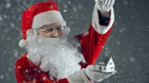 осадки : Santa Claus strewing confetti on house dummy, causing real snow