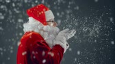 осадки : Side view of aged man in Santa Claus costume blowing confetti from palms causing snowstorm and turning to camera waving cheerfully Стоковые видеозаписи
