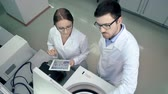 statistický : Above view of two lab colleagues testing pharmaceutical sample using centrifuge