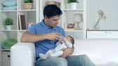 angel : Handsome young man sitting on sofa and holding his crying child feeding him with bottle