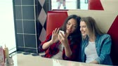 teknoloji : Two girls comfortably seated on sofa in cafe looking at smartphone screen Stok Video