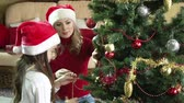 mama : Close up of mother and daughter decorating Christmas tree together