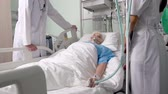 condição : Panoramic shot of clinical ward with post-surgical elderly patient in air mask talking to doctor and nurse