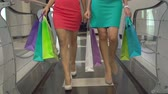 de vendas : Low section of two women carrying bags with purchases strolling in store in slow motion Stock Footage