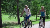 транспорт : Sportive couple cycling in park and blissfully talking Стоковые видеозаписи