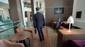беспроводной : Camera following businessman strolling along the hotel lobby and stopping to answer the phone call Стоковые видеозаписи