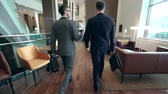 kierownik : Camera following two businessmen walking along hotel lobby and discussing issues