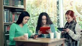 comprimido : Three girlfriends sitting in cafe with digital devices Stock Footage