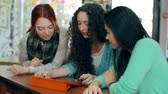 três : Three girls using one device and discussing something Stock Footage