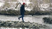 margem do rio : Guy walking along the stony shore of the river Stock Footage
