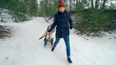 снежный : Tracking shot of man approaching camera running and pulling sleds with his girlfriend