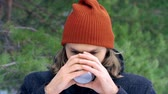 risonho : Close up of young man drinking hot tea on a winter day
