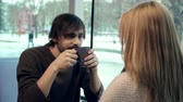 amor : Close up of handsome man talking to his girlfriend seated with her back to the camera in a cafe