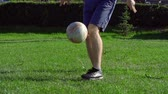 pontapé : Low section of unrecognizable freestyler juggling with a ball on green grass Stock Footage