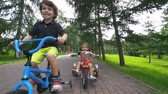 dva lidé : Handheld shot of two little cyclists approaching camera