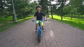 Little boy approaching camera cycling in park in slow motion