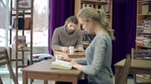 estudantes : Dolly of man setting his eyes on pretty girl reading a book in cafe