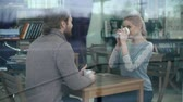 valentim : Through the cafe window shot of two friends drinking coffee and talking