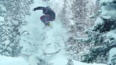 colidir : Slow motion of crazy fearless snowboarder freeriding in the forest and jumping from the hill crashing against pine tree