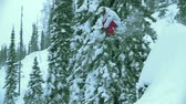 топ : Camera following freeskier jumping down the steep rock in slow motion