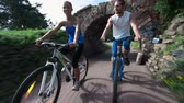 comum : Couple of young cyclists riding along the park and having fun