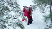 tremer : Slow motion of two little friends running through deep snow and playing with tree branches in the forest
