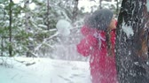 piscar : Little girl hiding behind the tree from snowball thrown at her and tossing handful of snow in defense