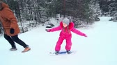 string : Side view tracking shot of little girl trying to maintain balance on snowskate pulled by her father