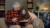 wróżka : Close up of grandfather seated on sofa reading a book to his granddaughter