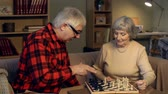 checkmate : Senior couple playing chess, man explaining the rules of the game to his wife