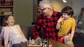 checkmate : Little girl fiddling around with chess pieces during game with her grandfather Stock Footage