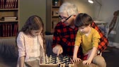 checkmate : Little girl playing chess with her granddad trying to figure out her next move