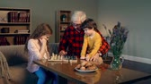 três : Dolly in of children playing chess with their grandfather in the cozy living room
