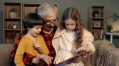 беспроводной : Kids spending time with their grandfather using digital tab Стоковые видеозаписи
