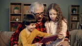 tabuleta digital : Close up of two siblings sitting on grandfather's lap and playing video games