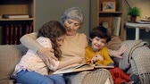 pastime : Affectionate granny cuddling with her grandchildren on the sofa while reading a book