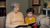 wróżka : Close up of grandmother reading aloud to her grandson