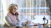 contato : Business woman having a conversation on the phone at the cafe table Stock Footage