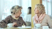 confidencial : Waist up shot of mid-aged and senior woman sitting at the table and having joyful conversation