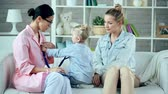 mama : Pediatrician and little patient changing roles, child using stethoscope Wideo