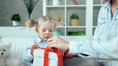 prezent : Cropped unrecognizable mother helping daughter to untie the ribbon off gift box