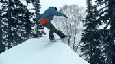 colinas : Freerider reaching mountain peak and turning snowboard back down in slow motion Stock Footage