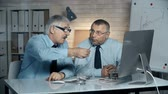 informace : Close up of two businessmen seated at table and discussing visual data on computer screen