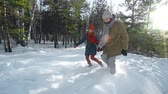 bem estar : Family of three enjoying winter stroll jumping in deep snow