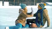 кататься на коньках : Couple just fallen down on ice at the skating rink, laughing