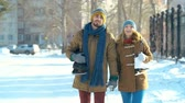ходить : Static shot of young couple with skates approaching camera