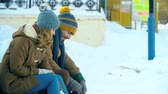 кататься на коньках : Tilt up of young sportive couple changing boots for skates on park bench Стоковые видеозаписи