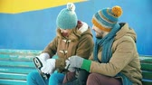 pastime : Close up of two young people putting their skates on