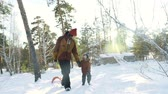 rodzina : Shaky camera tracking shot of father walking with his son through the woods in slow motion Wideo
