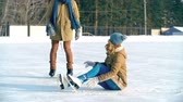 ajuda : Pretty girl sitting on ice in skates dusting her clothes down from snow, guy helping her up